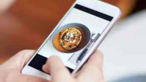 Girl taking photo of food on cell phone
